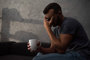 Lonely crying man holding cup of coffee sitting at home stock vector