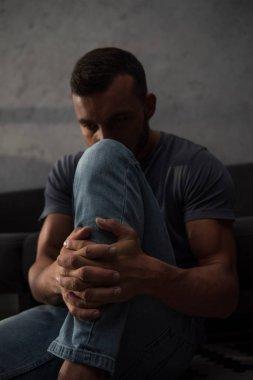 upset depressed man sitting at home, selective focus