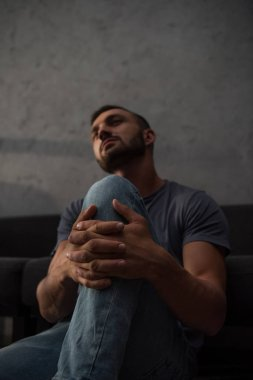 upset man in grief sitting on floor at home, selective focus