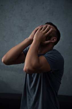 upset depressed man closing face with hands