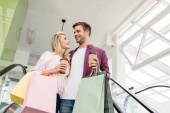 Fényképek alacsony, szög, kilátás a fiatal pár, a vásárlók és papír táskák kávéscsészét a mozgólépcső plázában