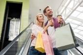 Fényképek fiatal nő, papír csésze kávé és rámutatva, hogy barátja a mozgólépcső Mall bevásárló táskák