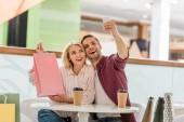 Fényképek ember vesz selfie barátnője bemutató bevásárló táska eldobható csésze kávé, kávézó asztal