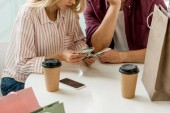 partial view of young couple counting cash money at table with coffee cups in cafe