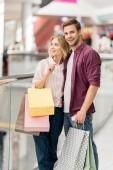 mladý, usměvavý pár s nákupní tašky a smartphone v nákupní centrum