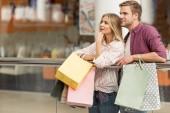 mosolygó pár vásárlók papír táskák állandó shopping mall