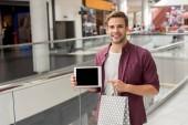 mladý pohledný muž s nákupní taškou ukazující prstem na digitální tablet s prázdnou obrazovkou na mall