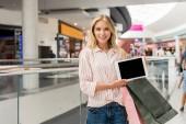 mladá usměvavá žena s nákupní tašky ukazující digitální tabletu s prázdnou obrazovkou na mall