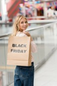 Fotografie smiling young woman holding paper bag with lettering black friday and looking at camera at shopping mall