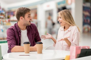shocked young woman gesturing by hands and looking at boyfriend while he sitting near at table with coffee cups in cafe
