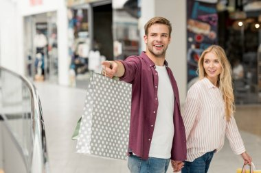 selective focus of smiling young man with shopping bags pointing to girlfriend walking near at shopping mall
