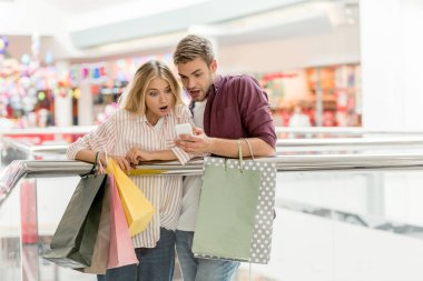 young shocked couple with paper bags looking at smartphone in shopping mall