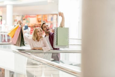 selective focus of young smiling couple of shoppers with taking selfie with shopping bags at mall