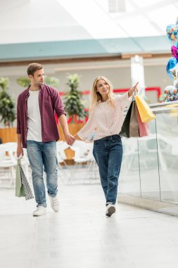 beautiful young woman with shopping bags pointing to boyfriend walking near at shopping mall