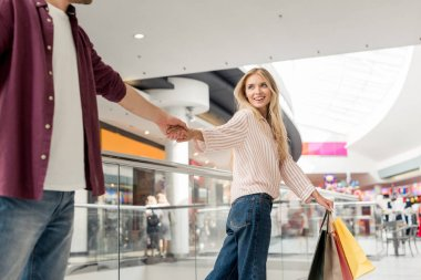 cropped image of man holding hand of girlfriend with shopping bags while she leading him at mall