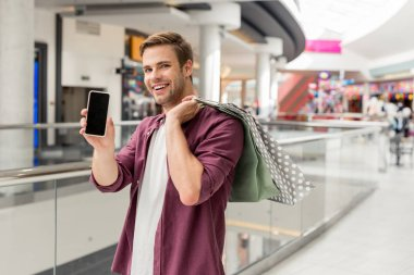 smiling young man with shopping bags showing smartphone with blank screen at mall