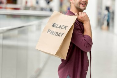 partial view of man holding paper with lettering black friday at shopping mall