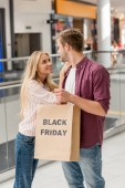 Fotografie smiling young couple of shoppers holding paper bag with lettering black friday at shopping mall