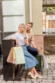 Fotografie stylish couple with shopping bags and paper cups of coffee standing near piano at urban street