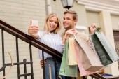 usmíval se mladý pár s papírové sáčky s selfie na smartphone poblíž obchodu na městské ulici