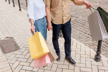 cropped image of stylish couple of shoppers with paper bags standing on street