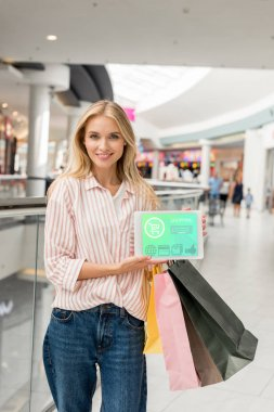 beautiful young woman with paper bags showing digital tablet with shopping on screen at mall
