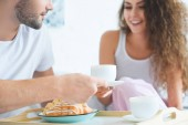 Fotografie cropped shot of happy young couple having croissants and coffee for breakfast in bed