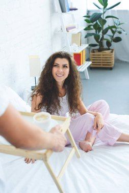 cropped shot of man bringing breakfast to beautiful smiling girlfriend in bed
