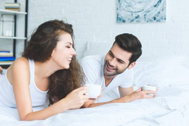 cheerful young couple in pajamas holding cups of coffee and lying on bed