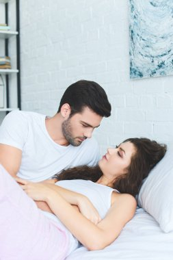 handsome young man looking at beautiful girlfriend lying on bed