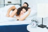 vista ravvicinata della sveglia e bella giovane coppia dorme nel letto dietro