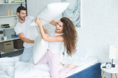 Fotografie happy young couple in pajamas fighting with pillows on bed