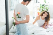 Photo young man hiding rose flower and looking at smiling girlfriend in bedroom