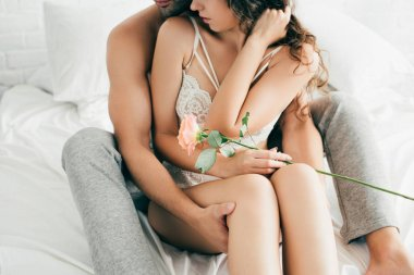 cropped shot of young man hugging seductive girlfriend with rose flower on bed