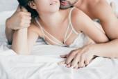 Fotografie Schuss von sexy junge Paar Hand in Hand im Vorspiel auf Bett beschnitten