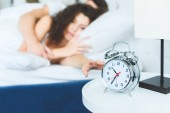 Photo close-up view of alarm clock and young couple waking up in bed