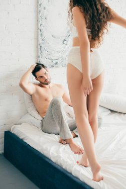 handsome young man looking at sexy girlfriend in lingerie standing on bed