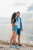 Fotografie beautiful happy couple hugging on beach near sea