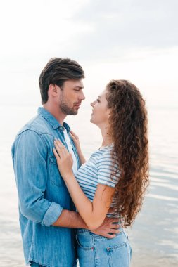 Beautiful young couple embracing near sea stock vector