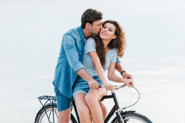beautiful couple sitting on bicycle near sea, man kissing his girlfriend
