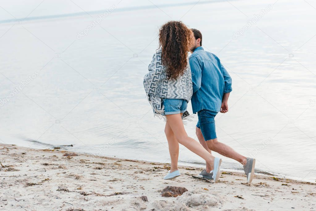 back view of young couple running on seashore
