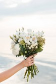 cropped view of woman holding beautiful bouquet with white flowers