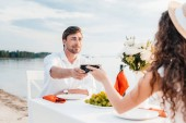 young couple clinking with wineglasses during romantic date on beach