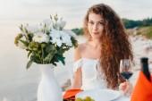 Fényképek vonzó boldog lány pohár a bor a romantikus dátum beach