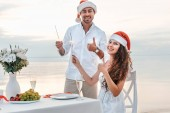 happy couple in santa hats showing thumbs up and celebrating christmas with sparklers on beach
