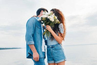 couple embracing and kissing behind the bouquet near sea