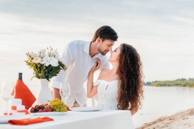 beautiful couple kissing on romantic date on seashore