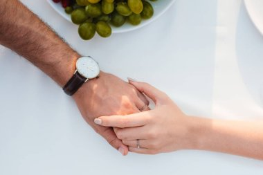 couple holding hands after propose in romantic date