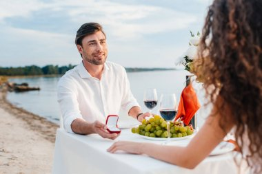 smiling boyfriend making propose with ring to girlfriend in romantic date outdoors