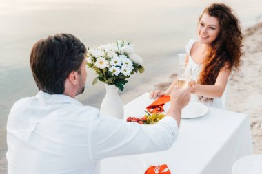 man and woman toasting with champagne glasses during romantic date on beach